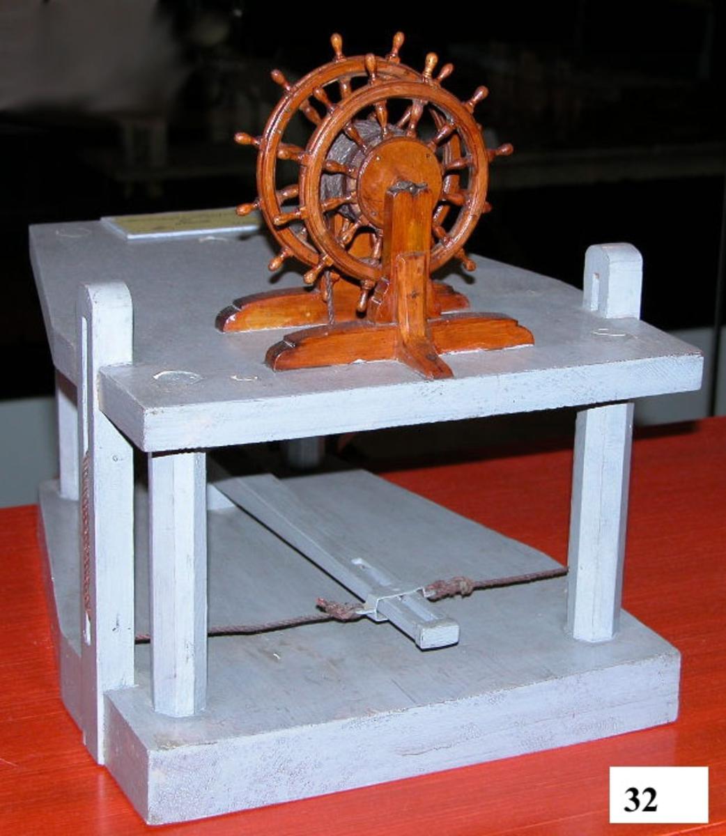 Modell av fartygsratt, drill, uppställda på ett tvådäckat plan motsvarande ett däck och utrymmet därunder. Drillen består av två fartygsrattar med trumma emellan med drilltåg, som löper under däcket via block och är fästat till styrpinnen. Drill och dess ställning är fernissat, övrigt gråmålat.
