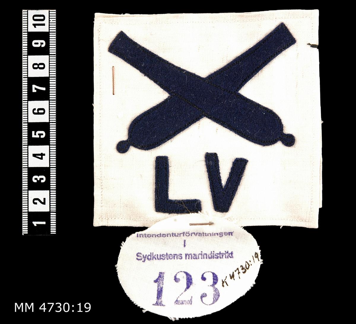 Yrkesbeteckning, kanoner med LV, M /24. Av blått kläde på vit botten. För riktare vid luftvärnskanon. 2 stycken.