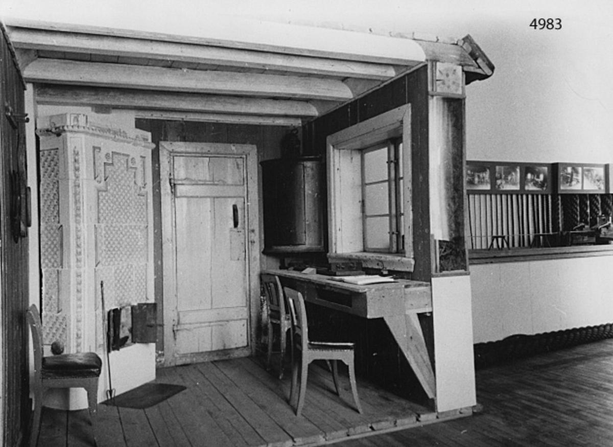 Gamla Tjärhuset å Lindholmen, sektion. Skuren genom Repslagarmästarens kammare och inmonterad i den sal i gamla museet, som visar utvecklingen inom repslageriverksamheten å ÖVK. Ytterväggen finns med. Väggfyllning med gammalt tjärdrev. På taket tegelpannor, som tillhört huset. Den externa väggytan är gulmålad, med dörrkarmen i grå färg.