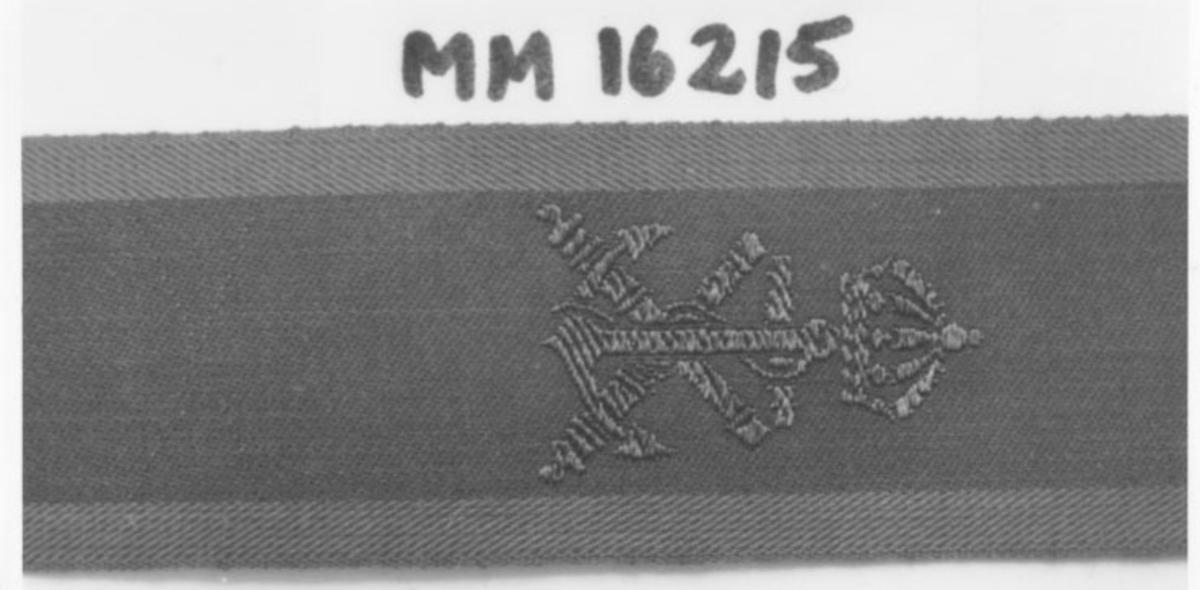 Textilband med tre gröna längsgående fält; märkning för vikning. Vapenslagstecken för Marinen, två korslagda kanonrör med på sig ett ankare krönt med krona; invävt i bronsfärgad tråd.