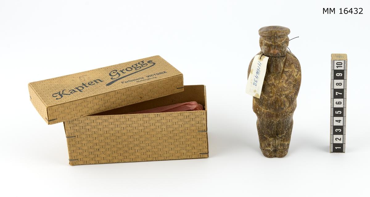 Tvål. Föreställer man i helfigur iförd kaptensuniform, händerna knäppta på magen. Förvaras i originalförpackning märkt på locket: Kapten Grogg parfumerie Victoria Helsingborg.