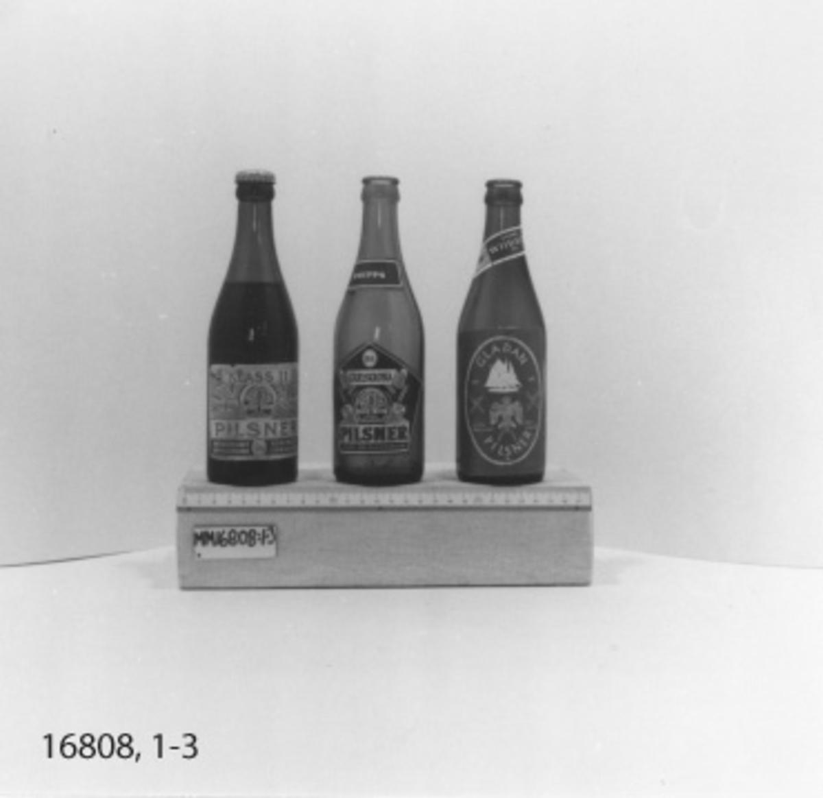 """Flaska, 33 cl, i brunt glas utan kapsyl. Stor rektangulär etikett med  vitt tryck på blå botten med text: """"Gladan pilsner Glada bryggeriet  sjörullad 1947 1976"""" Inom ram av rep silhuett av skonerten Gladan, samt stiliserad teckning av rovfågeln gladan samt på vardera sida två korslagda gångsspelsspakar. Under denna etidett finns en oval med text= """"Wibroe Pilsner Öl Helsingör"""". Liten etikett på flaskans hals """"Dansk Wibroe öl, ölet fra Hamlets By klasse IIB"""". I botten  *""""PLM 72 L10 SS inom vågsymbol, taggad kant."""