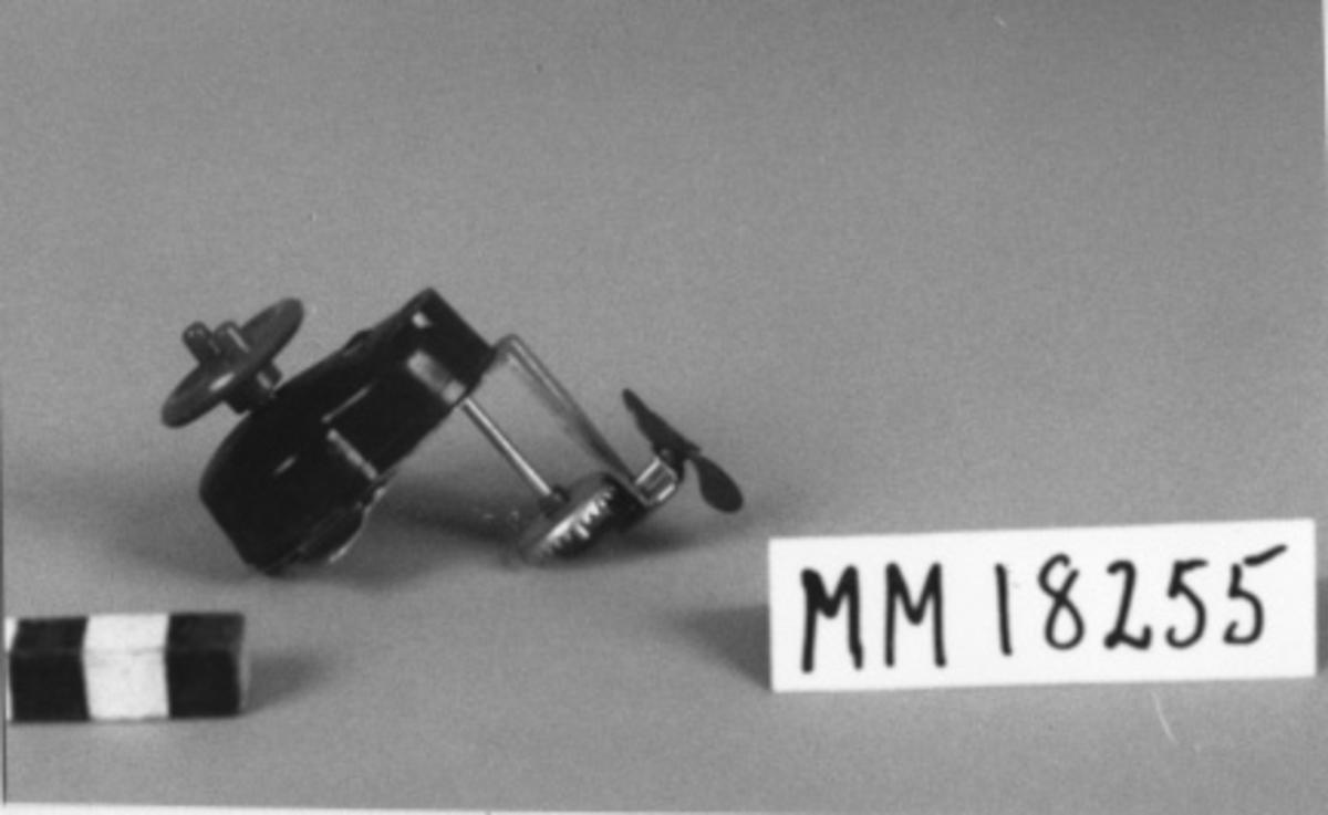 """Utombordsmotor till leksakbåt bestående av hölje av formpressat plastmaterial, rött och svartmarmorerat samt försett med ingjuten text: """"KNOP"""" samt  """"K. W.Ö."""" Rund plastratt överst på höljet försedd med två spakar som vid vridning  spänner den dolda fjädern. Propeller under motorn, sättes igång med hjälp av kugghjul. På motorns undersida sitter en oval bricka som skall fästas i båten och sedan inskjutes motorn i brickans falsar och kan på så vis även vridas i sidled. Motorn förvaras i en pappersask med tryck i rött och blått """"Utombordsmotorn Knop EN SVENSK NYHET FÖR POJKAR I ALLA ÅLDRAR"""" samt bruksanvisningen med mera."""