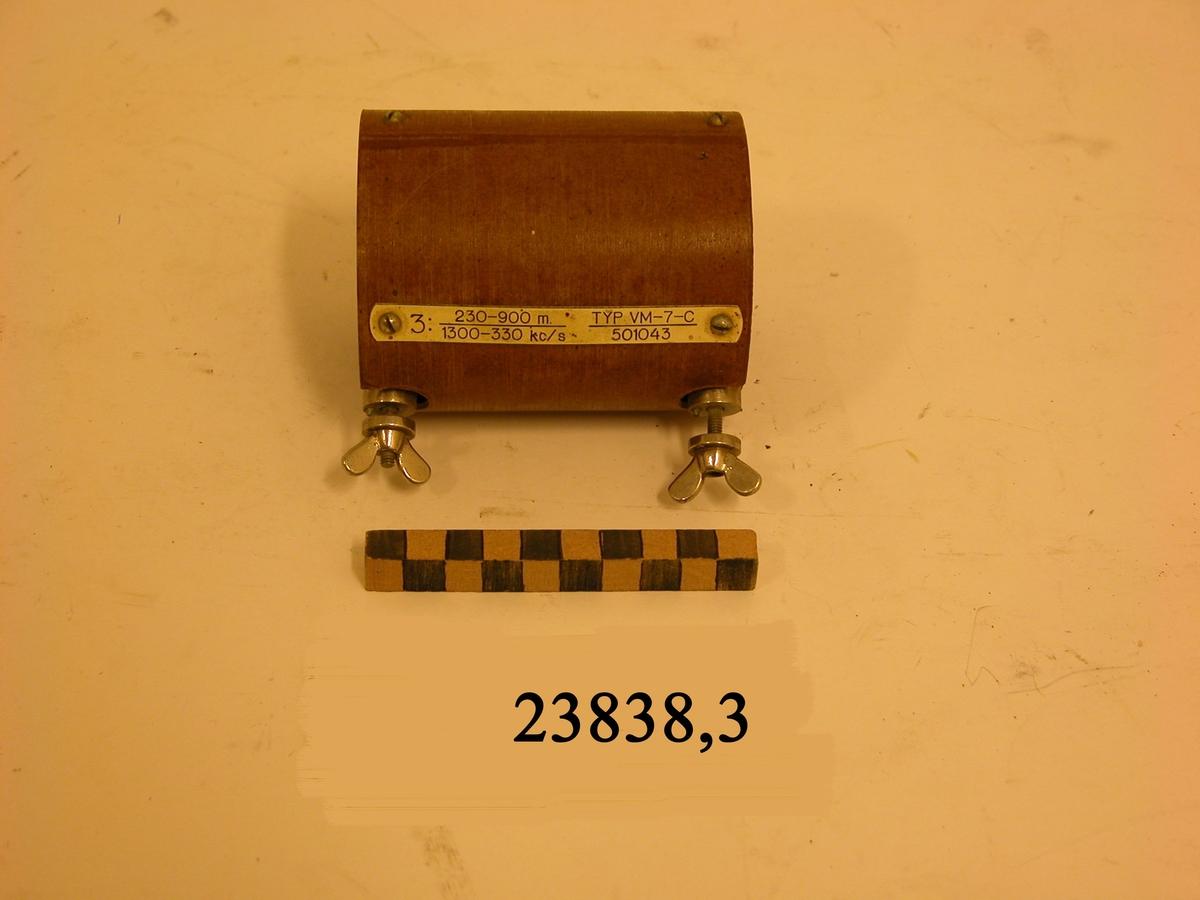 Ljusbrun cylinder med dubbla väggar och två skruvar av metall med vingmuttrar. På cylindern en fastskruvad bricka av plast med text : 3: 230-900 m. 1300-330 kc/s. TYP VM-7-C. 501043.