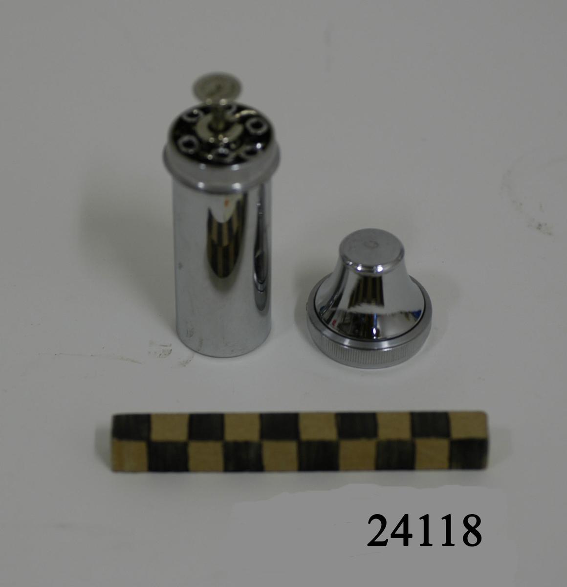 """Cylindriskt etui, fickbestick av förnicklat stål med konformat skruvlock. På lockets insida en stålfjäder. I behållaren urtag för, samt sex stycken kanyler och en injektionsspruta. Sprutan av metall och glas, blå gradering samt text: """"R:Co CC"""". Text i metallen: """"Orginal - Record""""."""