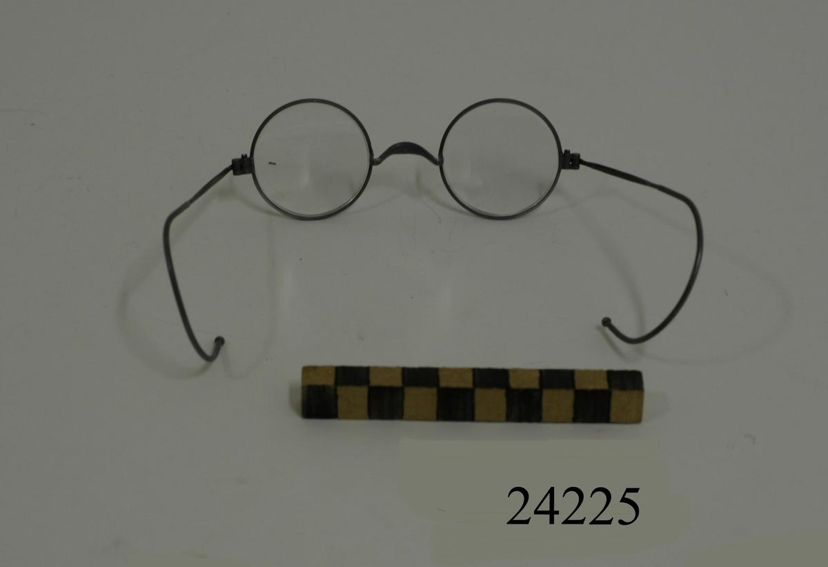 Glasögon med runda glas (D = 40 mm) infattade i runda bågar av grå metall. Skalmarna böjes bakom öronen. Glasögonen förvaras i grått plåtfodral med lock, MM 24226.