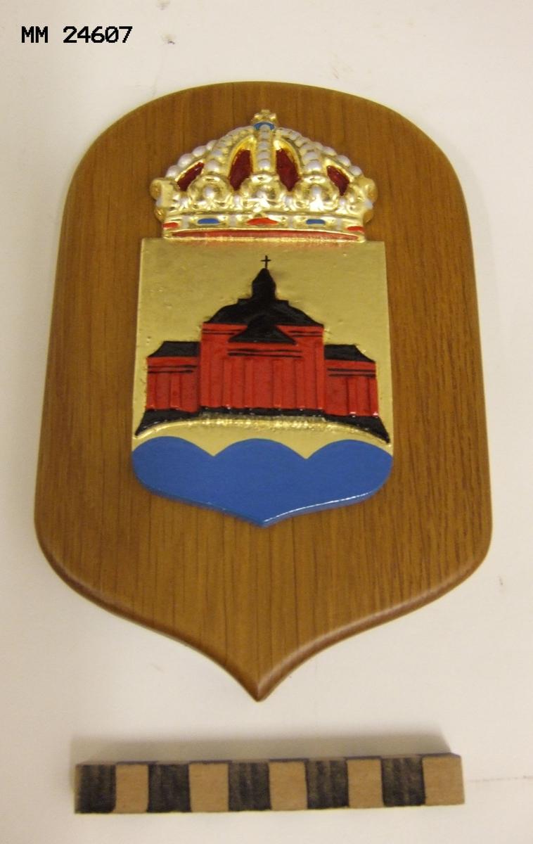 """Vapensköld, HMS Trossö. Krönt vapensköld av gjuten mässing monterad på brunbetsad platta av trä. Skölden gyllene och blå. På det gyllene fältet syns i rött och svart Amiralitetskyrkan (Ulrica Pia) i Karlskrona. På baksidan påklistrad lapp med text: """"SVENSK METALLKONST Tel. +4645584100 www.metallkonst.se""""."""