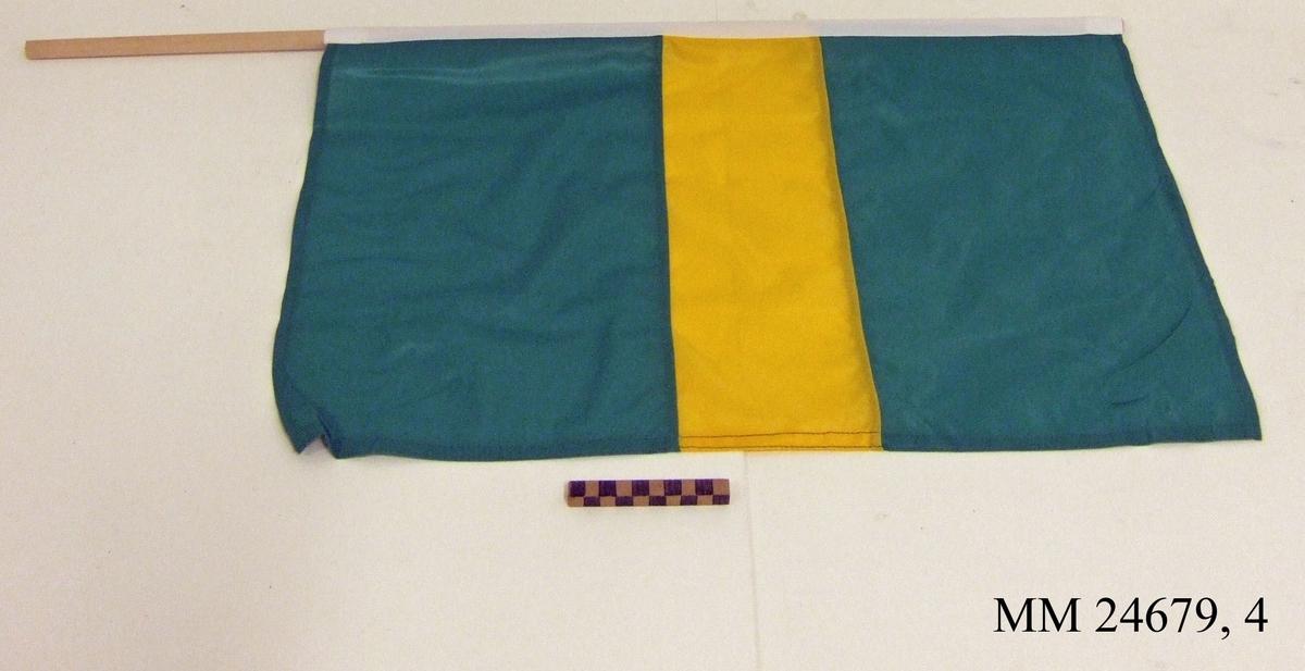 Manöverflagga på stång av trä. Flagga av grön nylon med gul hotisontal rand i mitten. Vitt lik trätt över rundstaven och fäst med häftklammer. Flaggan ligger i påse tillsammans med fem andra flaggor, sk. manöverflaggställ.