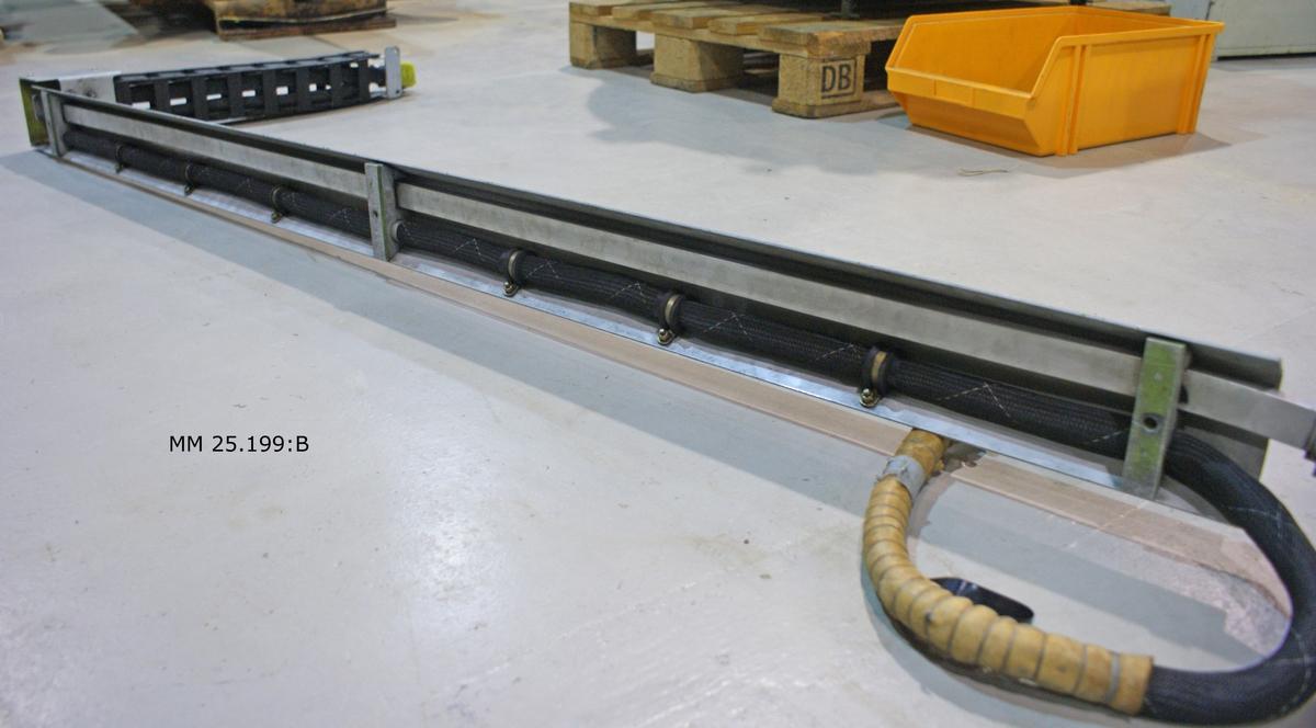 Grå u-formad metallränna som utgör kabelränna för vågledarkablarna. I ena änden sitter kontakter, i andra änden en svart plastarm som är ledad likt ett stridsvagnsband. Kontakter även i denna ände. I kabelrännan ligger svarta kablar som hålls fast med hjälp av metallbrickor som sitter över kablarna.
