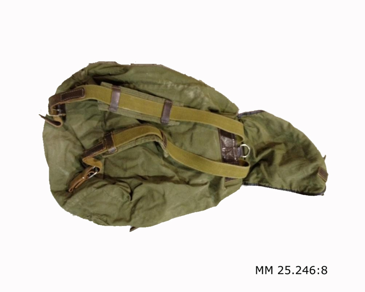 Grön ryggsäck i kraftigt tyg, kanske kanvas. Locket stängs med en läderrem. På yttersidan finns en ficka som kan stängas med ett lock med två läderremmar. På ryggsidan sitter två remmar att trä över axlarna i något mer olivtonat grönt textil.Längden kan regleras med hjälp av läderremmar som sitter vid fremmarnas nedre fästen.