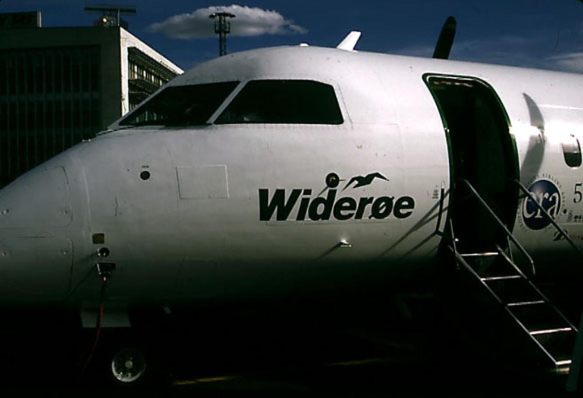 Lufthavn, 1 fly på bakken, DHC-8 (Dash 8) -300 LN-WFH fra Widerøe. Nesepartiet.Ingangsdøra er åpnet. Terminalbygningen i bakgrunnen.