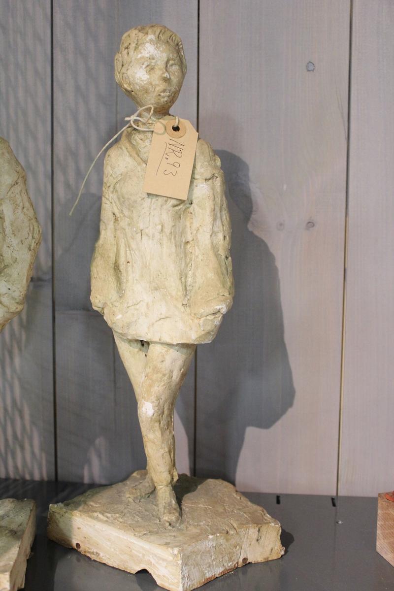 """Skulptur i gips av en ung kvinne med hendene i lomma. Tittel: """"På stripa i 50-årene"""" Vist på høstutstillingen i 50-årene.  Se også nr.176 nr.175. nr.174, nr.092 og nr.094. Skulpturen i bronse er 170cm. høy og var en gave fra Kristiansand og Oplands Privatbank til Kristiansand kommune i 1978. Står i Markensgate i Kristiansand."""