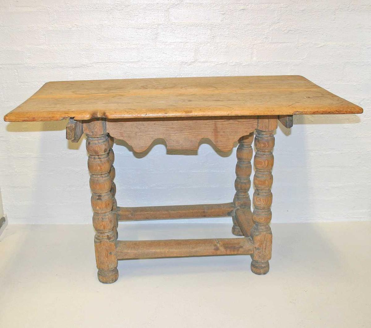 1 firkantet bord   Platen er 66 x 110 cm, høiden fra gulvet 70 cm. Platen er løs og hviler paa 4 føtter, der oventil og nedentil er forbundet med tværstykker. Føtterne dreiet i kuleformige avdelinger. Kjøpt av gaardbr. Johannes Rutlin, Sogndal