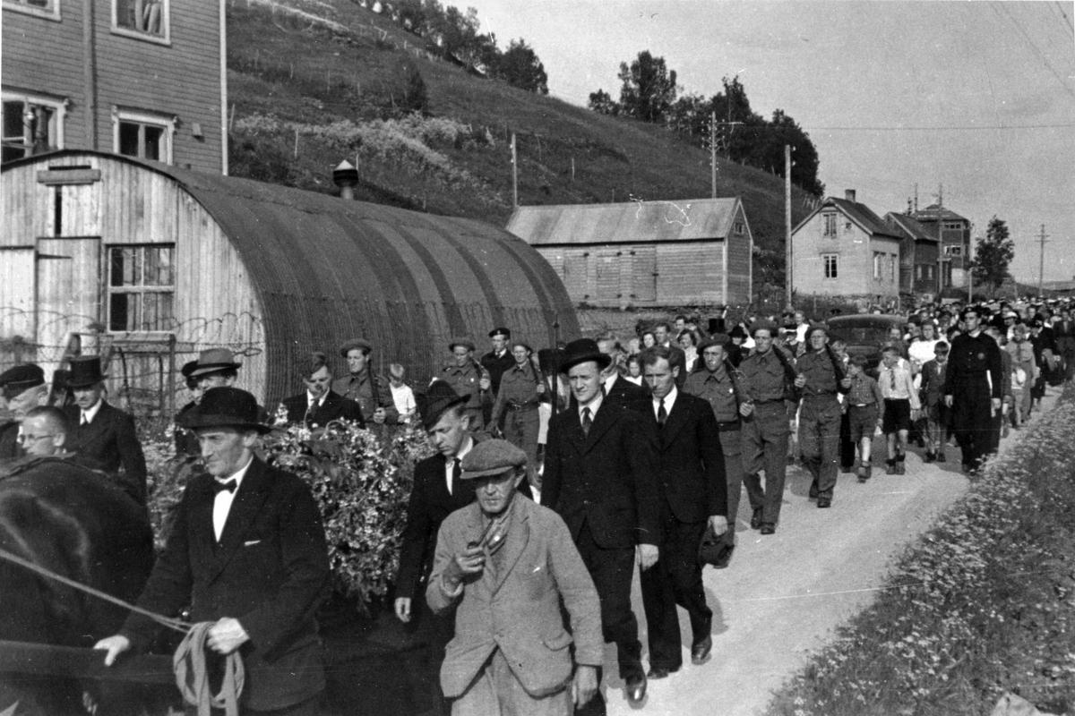Begravelsesfølget til Spilling og Pettersen fotografert på vei forbi Samaskolen, sommeren 1945. Alf Pettersens båre nærmest, flankert av kolleger (elektrikere). I forgrunnen vognmann Magnar Mikkelsen, og Hjalmar Dahl i grådress. Bak dem Kåre Andreassen og Arne Hay.
