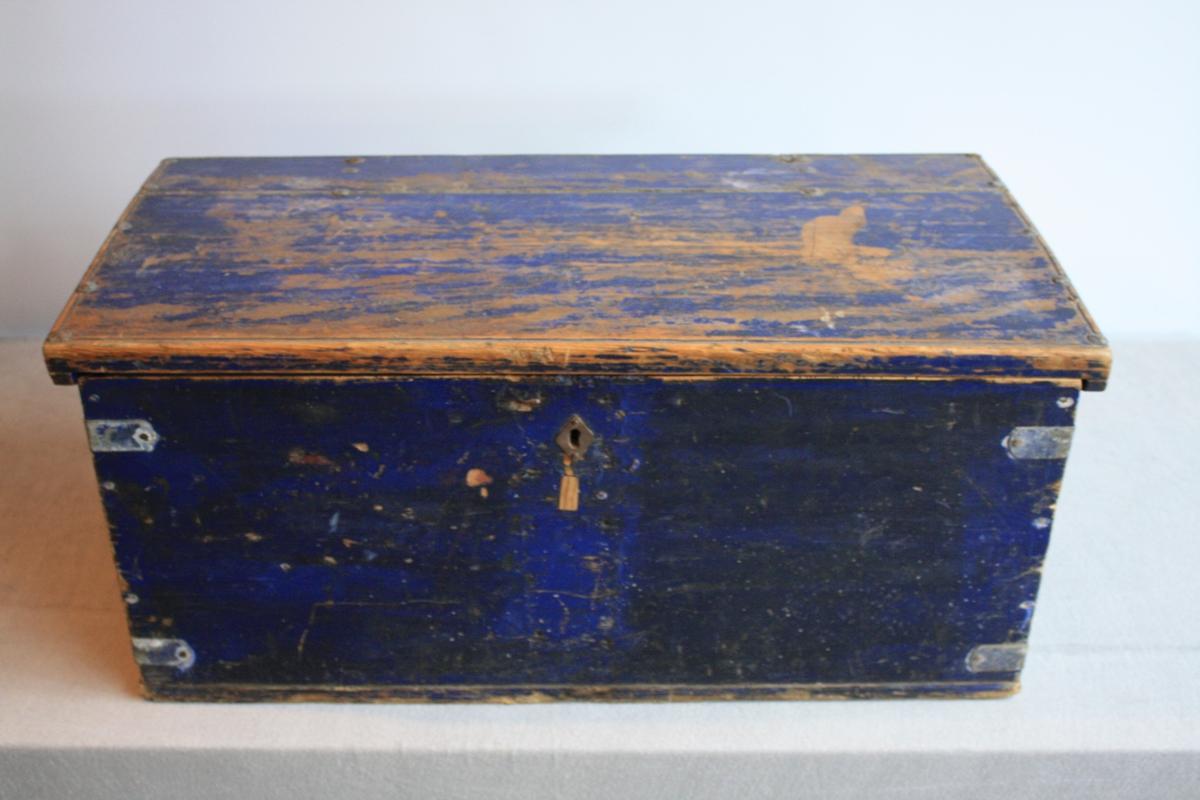 Blåmalt kiste med flatt lok. Handtak på begge sider. Spor etter at ein lås har blitt tatt vekk og at det har blitt satt in ein ny.