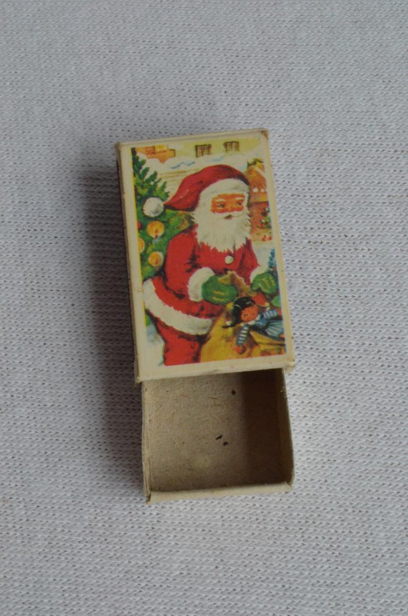 Fystikkeske med julemotiv. Motivet er ein julenisse med ein sekk leikar, i bakgrunnen står eit juletre.