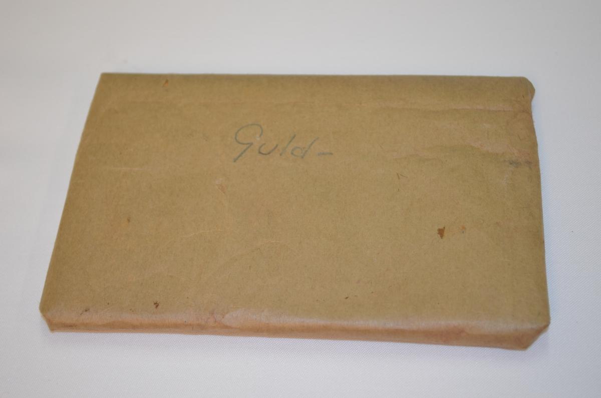 Flat rektangelforma gjenstand pakka inn i gråpapir. På framsida står det skriven Guld- med gråblyant. Kan godt innhalde utstyr til bokinnbindarfaget. Denne låg i ei verktøykasse frå ein boktrykkar.