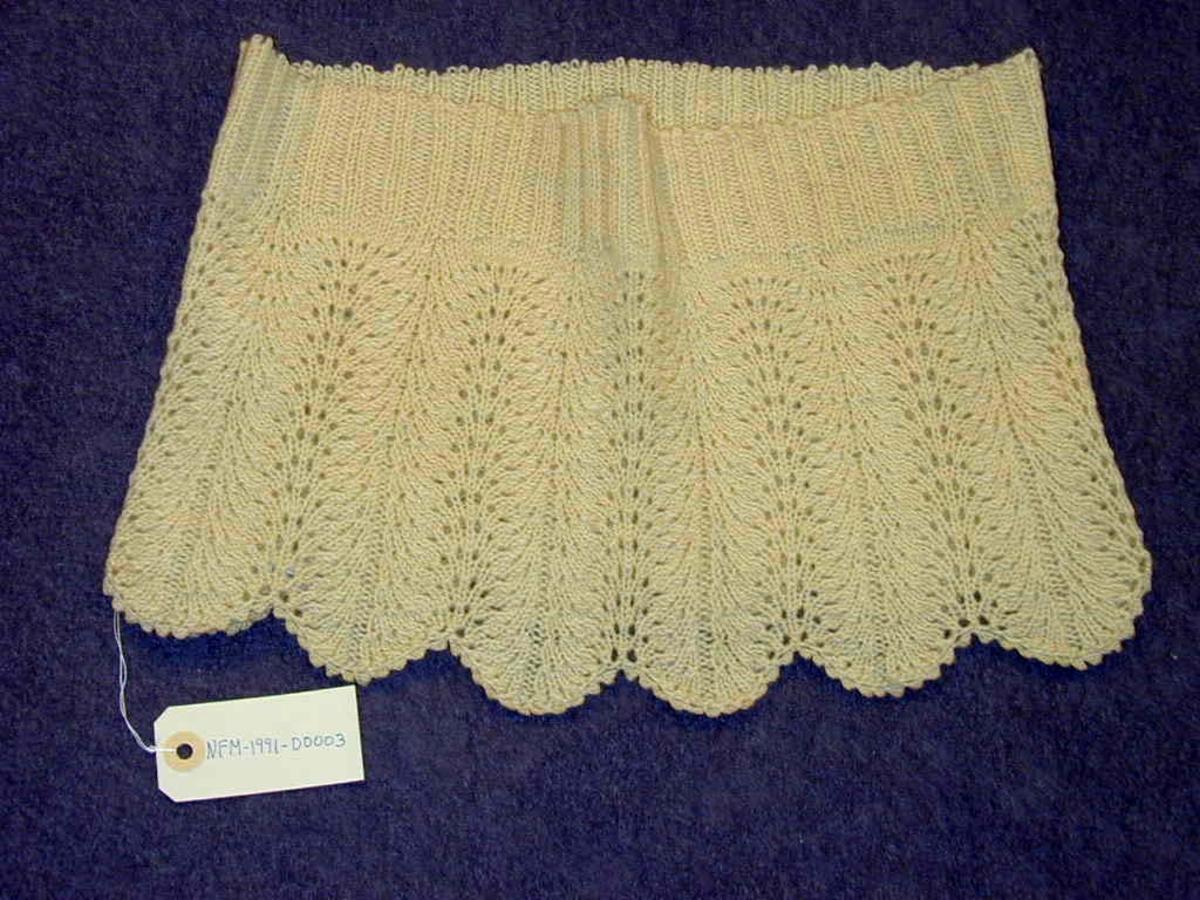 Uferdig strikkeplagg med lause maskar øvst. Truleg tenkt som nedste del av underkjole eller underskjørt til ung jente.