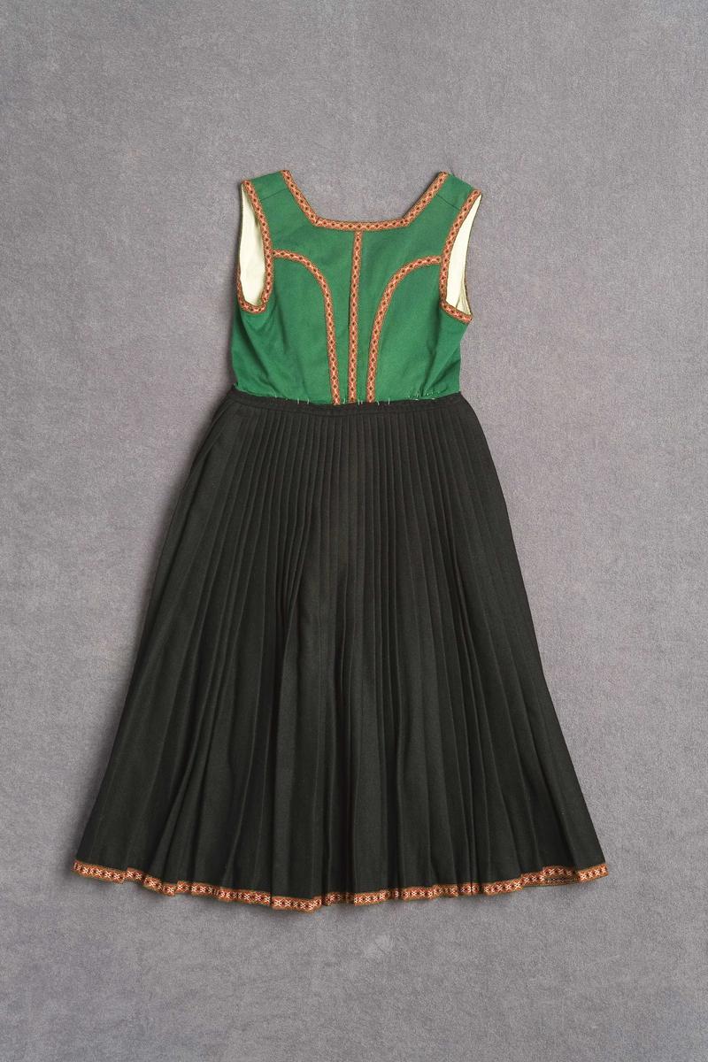 Nedst, i forlenging av det svarte stoffet, er sydd eit vove band med same fargane og nesten same mønsteret som bandet i livet (NFM.1993-00719), men er noko breiare