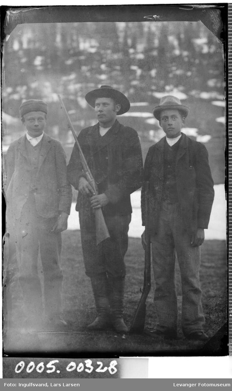 Gruppebilde av tre unge menn med geværer.