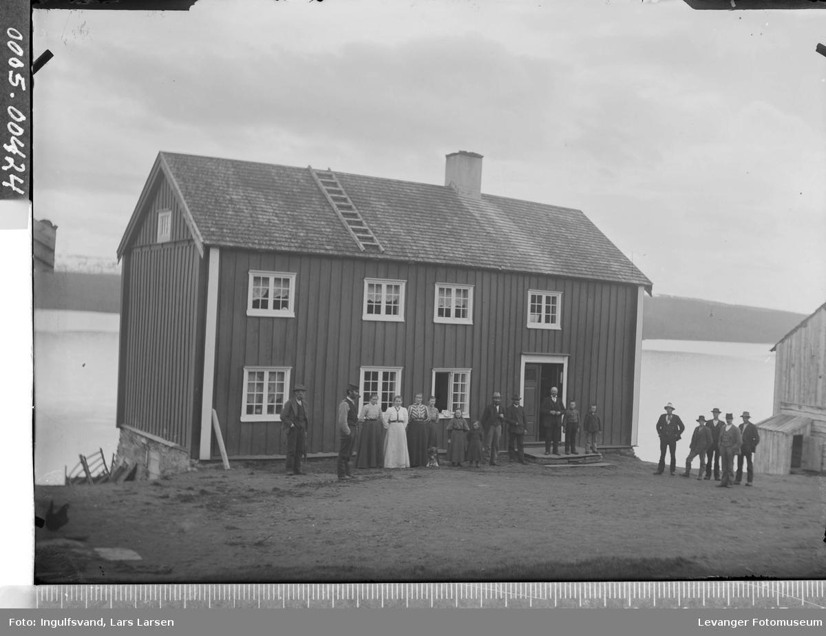 En gruppe mennesker foran et våningshus.