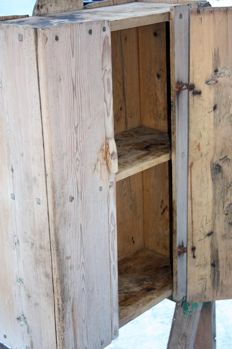 Skap for rett vegg med ei hylle og dør på 1/3 av framsida. Samansett med trepluggar. Midtplanken på ryggen er forlenga med eit hol øverst til oppheng.