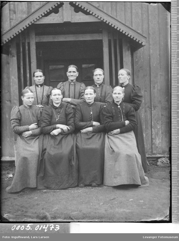 Gruppebilde av åtte kvinner foran et inngangsparti.