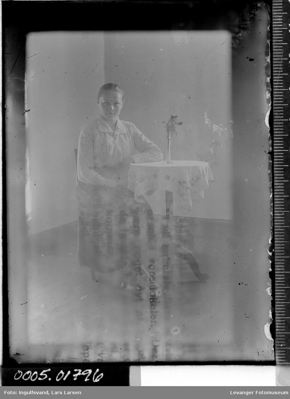Portrett av en kvinne ved et bord.