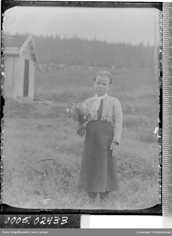 Portrett av jente som holder blomsterbukett i helfigur.