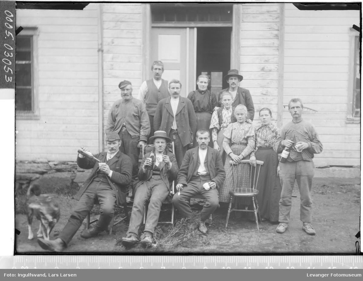 Gruppebilde av åtte menn og fire kvinner foran et inngangsparti.