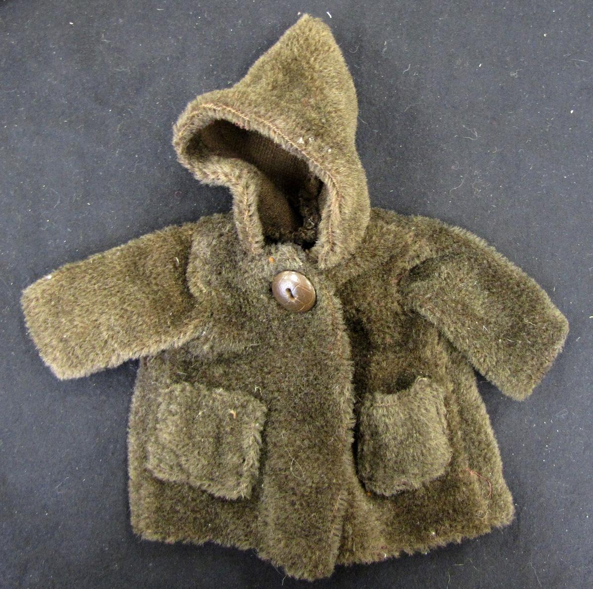 Kappa sydd luddigt syntettyg. Kappan har luva och två fickor samt knäpps med en knapp i halsen. Kappan har används till dockan ''Kajsa'' VM 22 788:1.