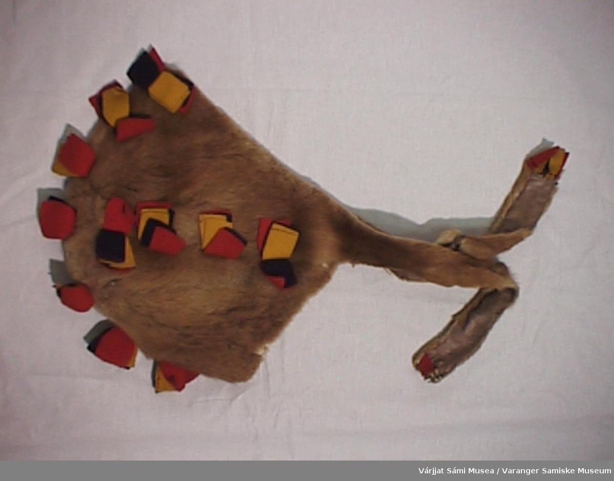 Damelue av skinn-hva slags skinn vites ikke. Lua er pyntet med kledestykker i rødt, blått og gult, ialt 15 stykker. Lua er trekt med brunt silkefor