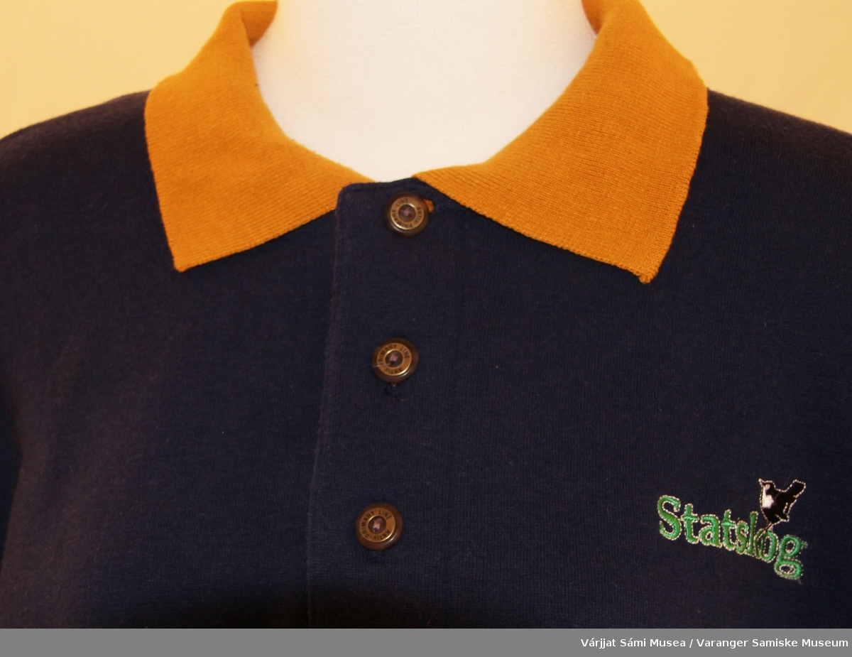 """En genser av bomullsjersey, unisex modell. Genseren er marineblå med Statskog logoen brodert i grønt (skrift), sort og hvitt (Fossekall) på brystet. Sennepsgul krage som lukkes med tre brune og messingfargede knapper foran på brystet. Den er merket """"Aktiv Primary Line"""" og er i størrelse XL."""