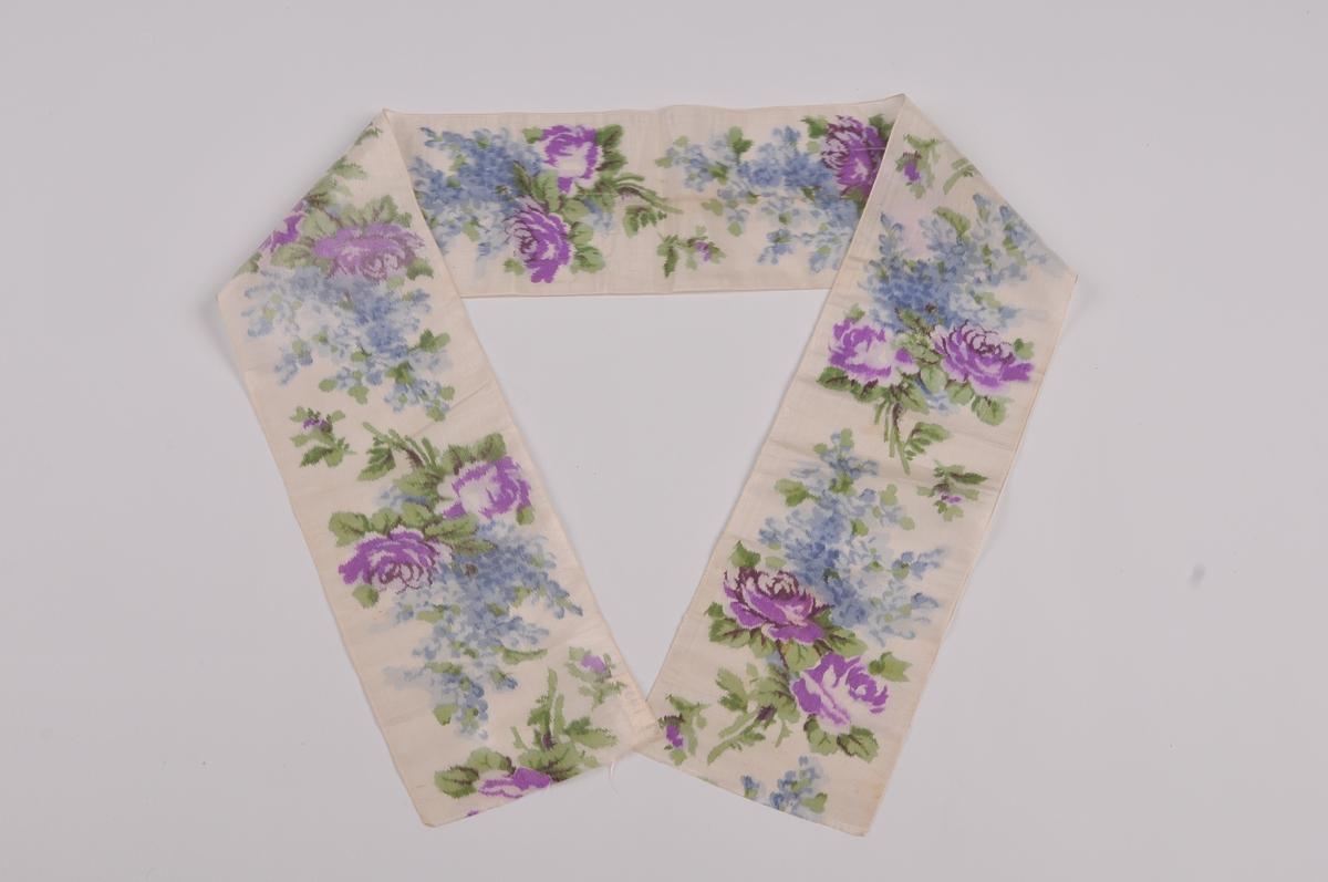 Silkeband med kvit botnfarge. Trykt rosemotiv i blått, fiolett og grønt.