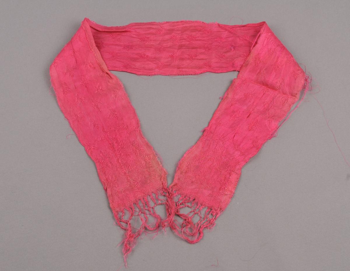 Ljos rosa silkesløyfe i blomemønstra damask. Knytte frynser på kortsidene. Jarekant på begge langsider.