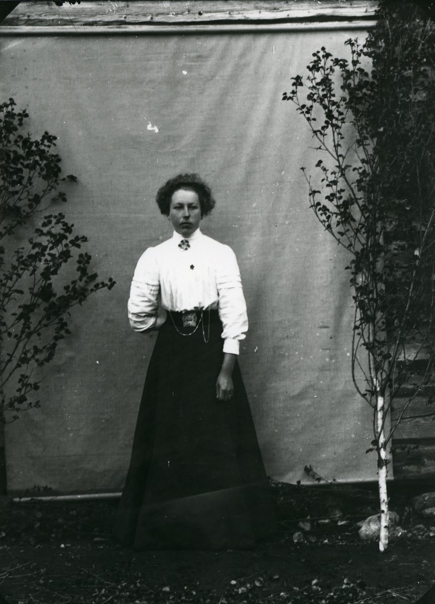 Kvinne i helfigur foran lerret
