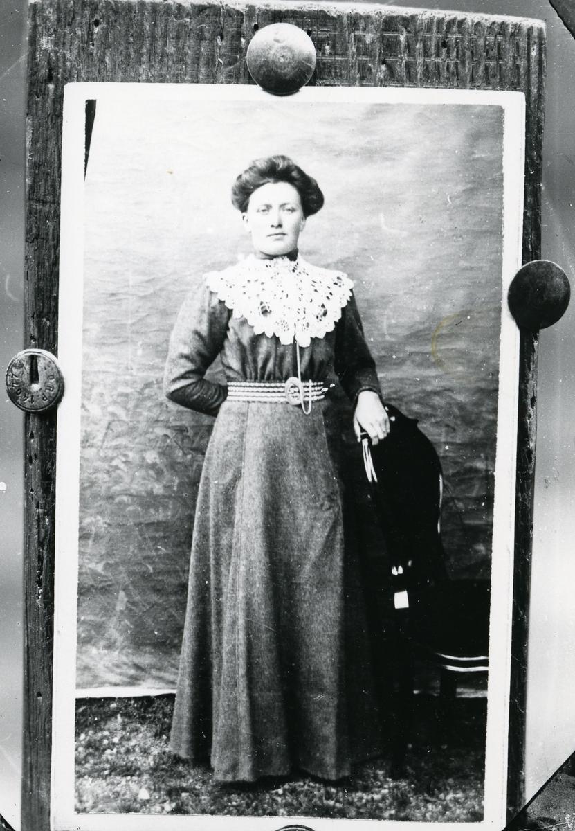 Fotografi av fotografi festet på treplate med tegnestifter. Stående kvinne i helfigur, med stol, lerretbakgrunn