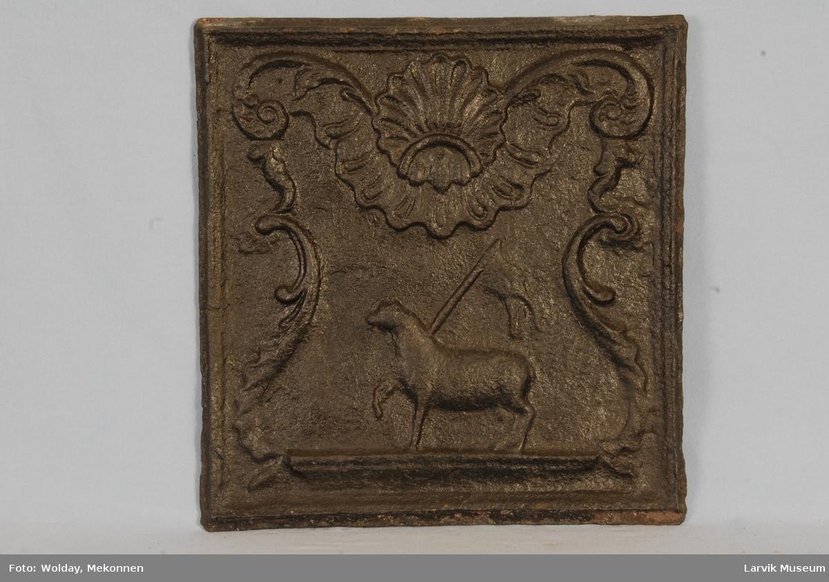 lam m/seiersfane (Kristussymbol) på lavt postament, omgitt av symmetrisk rokokko-ornamentikk...