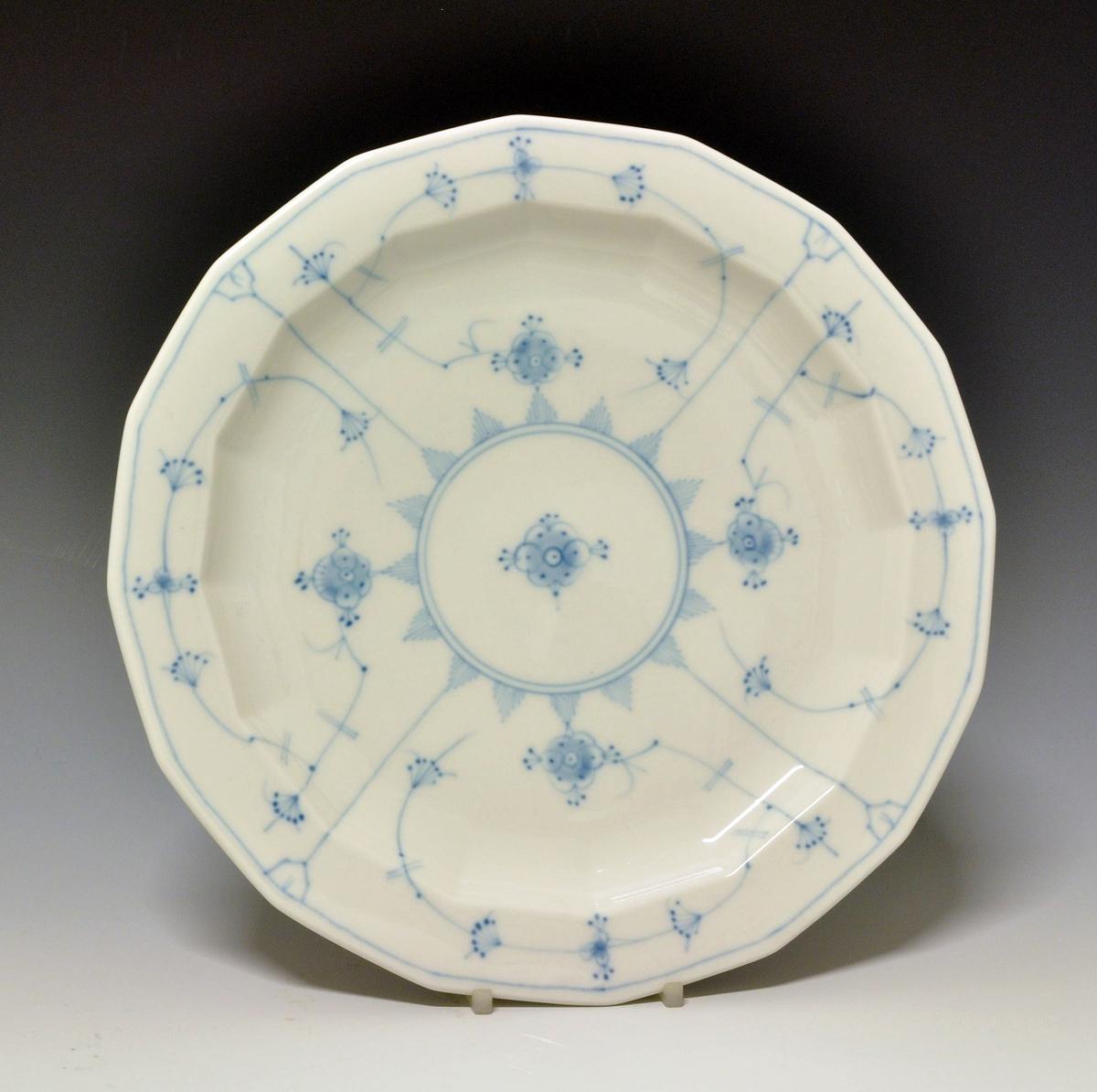 Flat tallerken i porselen. På fanen er flat med 16 kanter. Dekor: Stråmønster i blått Modell: 2575 Grethe Rønnings Oktavia