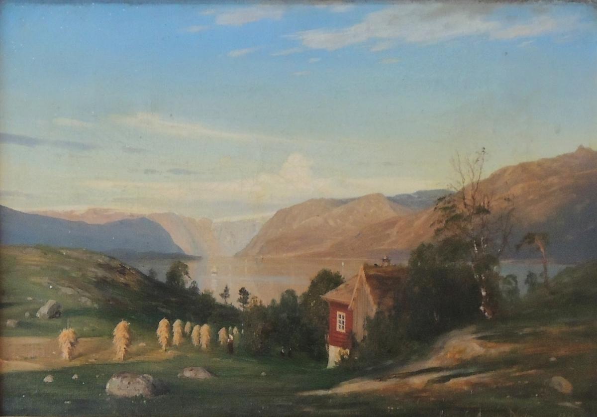 Fjell, fjord, rødt hus og høysåter.