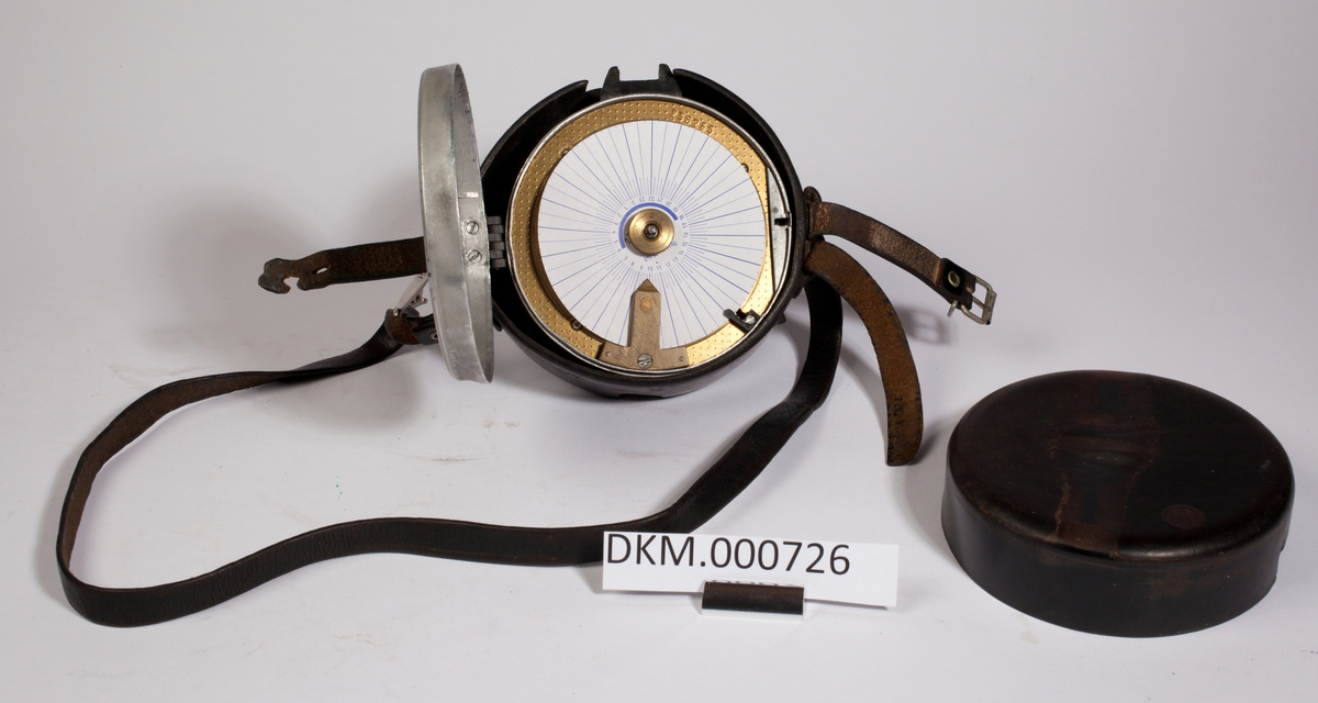 Rundt ur i metall som ligger i ett beskyttelsesdeksel av lær. En bærereim er festet til dekslet.