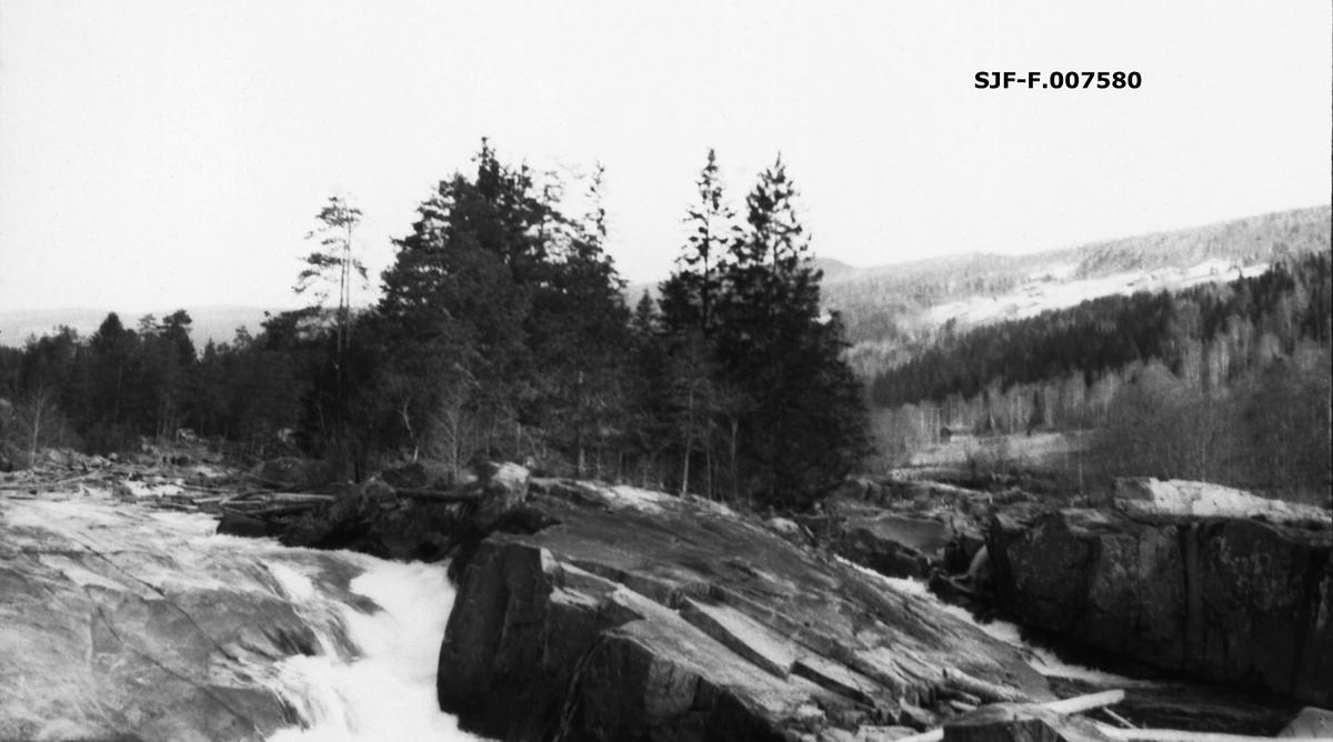 Fra Austbygdåe i Tinn i Telemark.  Fotografiet viser hvordan kvitskummende vann baner seg veg i revner over et berg.  Ettersom bildet er hentet fra arkivet til Skiensvassdragets Fellesfløtningsforening er det rimelig å anta at det er tatt for å vise en lokalitet der tømmerfløting må ha vært spesielt vanskelig.  Bildet er tatt i den nedre delen av vassdraget, litt ovenfor Rudsbrua.  I bakgrunnen ser vi ei li med skog og med gardsbruk omgitt av åpent dyrkingsland.  Dette er garden Berge og Bøengrende.