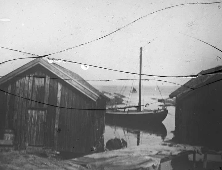 """""""Käringön. Käringöns fiskeläge med sjöbodar. Här syns en modern fiskebåt med motor.  Ute till havs syns en seglare."""""""