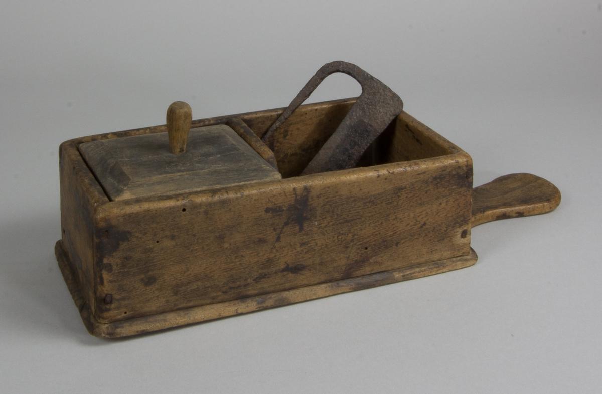 Elddonslåda tillverkad i trä. Rektagulär låda med två fack. Upptill balusterformat handtag av trä. Till ena facket finns ett lock med en snidad knopp. Med lådan följer elddon och flintstenar. Elddonet av platt stål, rektangulärt, med ett handtag utgående från ett av hörnen.