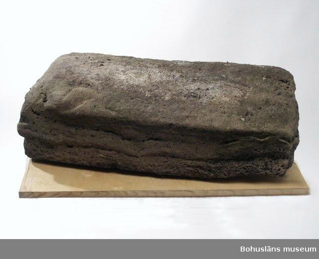 Rågummibal, närmast rektangulär klump 75 x 50 cm, oförpackad med svart/grå yta som liknar tjära, mjuk innanför ett hårdare skal. Mycket tung och ohanterlig. Solblekt.