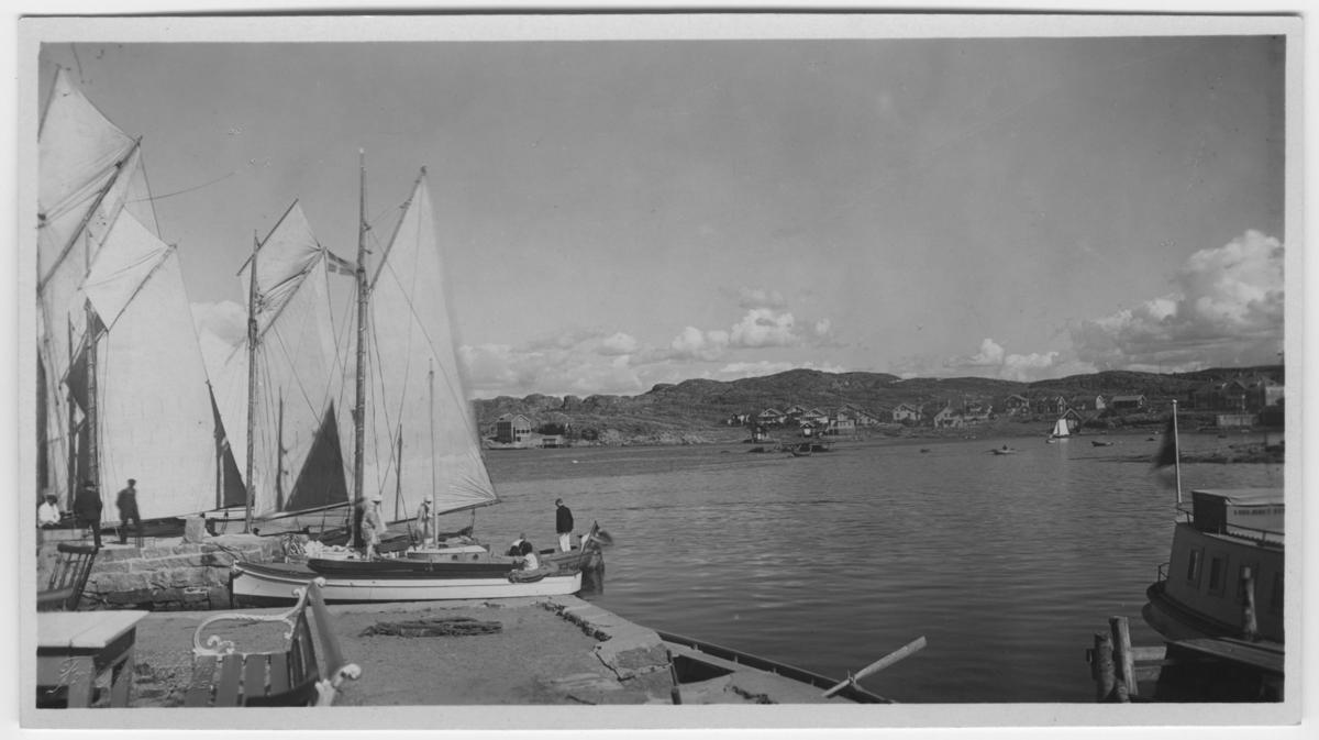 'Från ångbåtsbryggan, ''Klubben'' i fonden. Vy med segelbåtar och havet. I förgrunden bord, stol och träbäck. Människor vid båt. ::  :: Serie fotonr 1888-1963.'