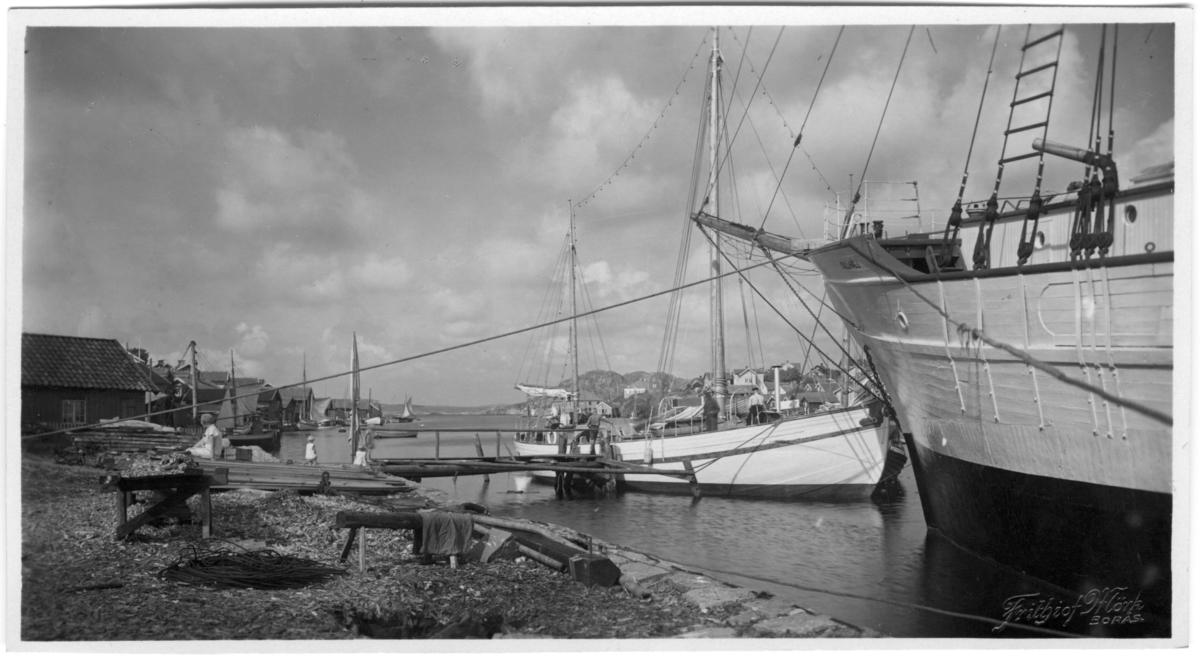 'Från Kilen, norrut. Båtar invid strand. 2 barn och 1 person på en hög träplankor på strand. På andra sidan hus på berghällar. ::  :: Serie fotonr 1888-1963.'