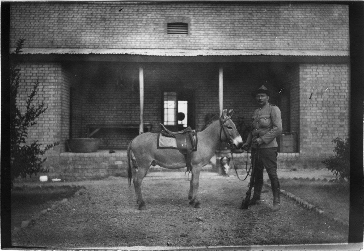 'Diverse fotografier från bl.a. dåvarande Nordrhodesia, nu Zambia, tagna av Konsul Magnus Leijer. ::  :: En man hållande i en åsnas tyglar står på grusgången framför en tegelbyggnad med veranda. Mannen håller i ett gevär.'