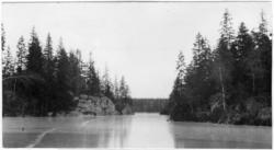 'Vy med sjö med trädklädda berg på sidorna. Gran mestadels.