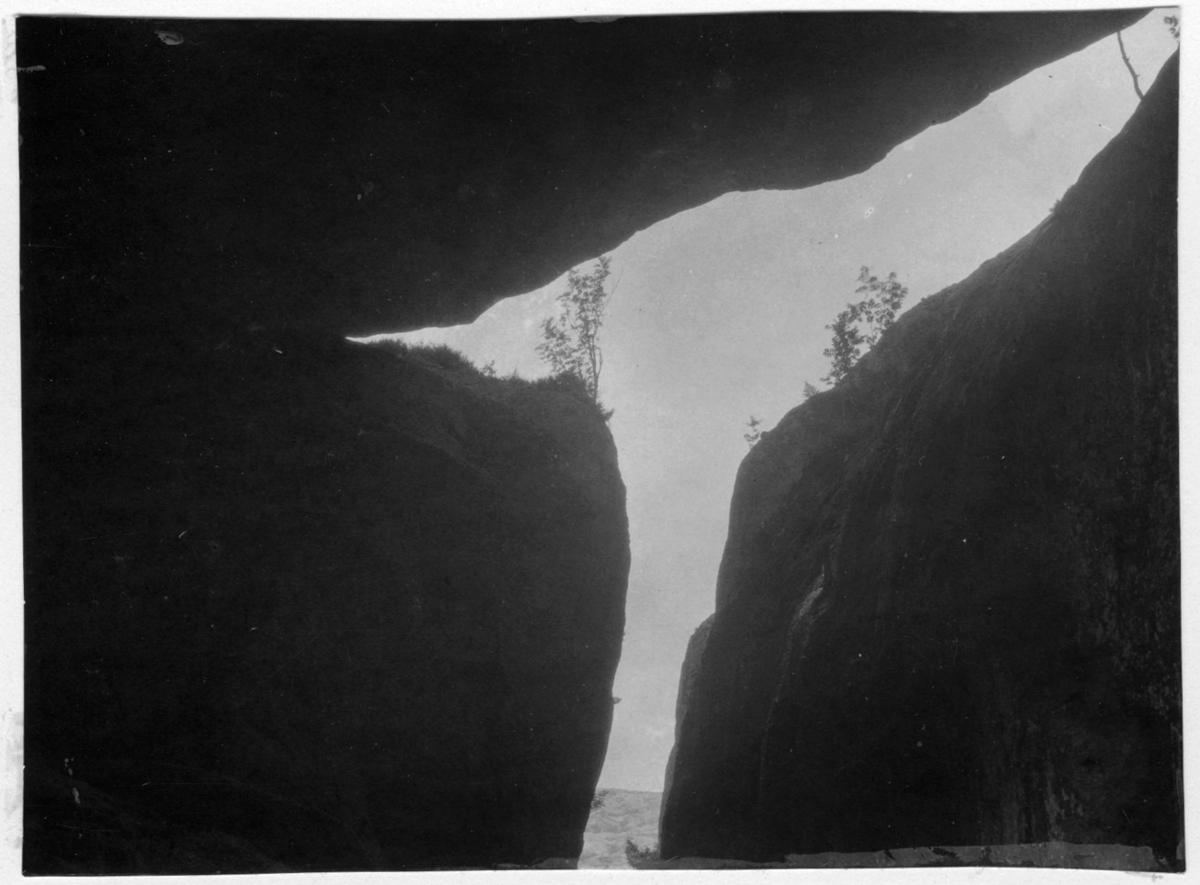 'Bildtext: ''Grotta och klova.'' Bild tagen inigrån grotta och ut genom klyfta. ::  :: Fotonr. 7046:85-118 indelade som ''Geologiska bilder från Göteborgs- och Bohus län.'' Ingår i serie med fotonr. 7046:1-383, 7047:1-33 och 7048:1-67 med bilder från  Länsjägmästare John Lindners bildarkiv.'